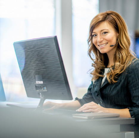 woman with a headset sitting at a computer